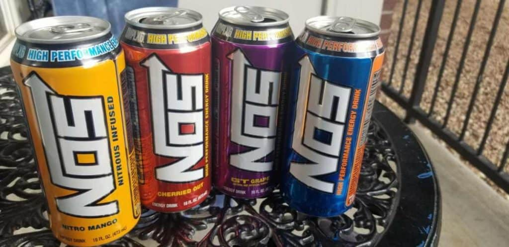 Four cans of NOS energy drinks in different flavors.