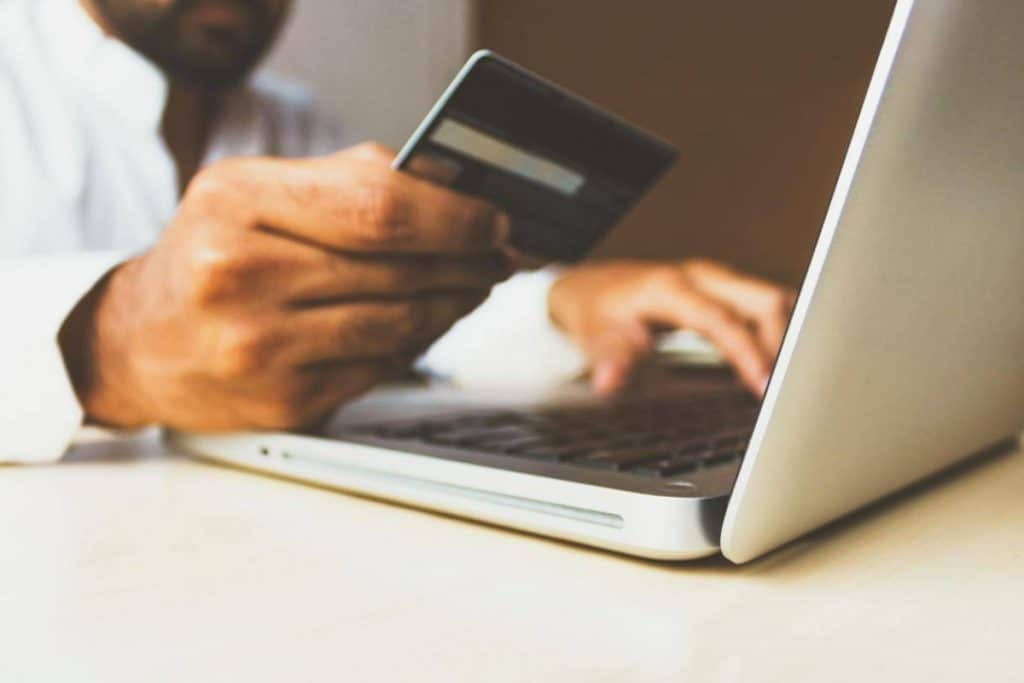 A person holding a credit card for online purchases.