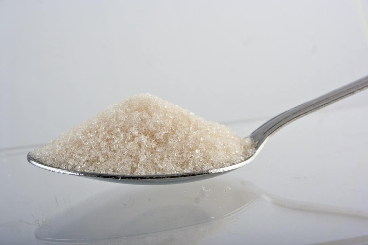 A photo of added sugar in a spoon, with a white background.