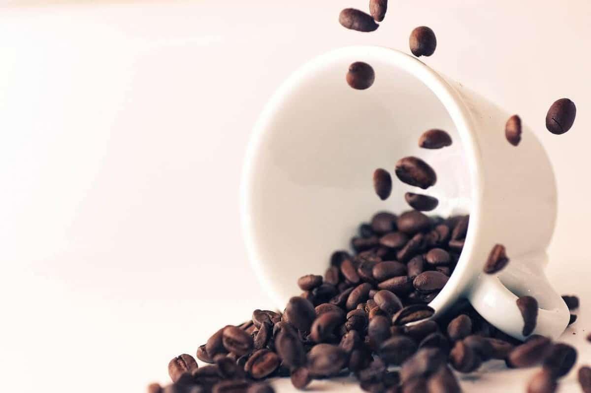 A photo of coffee beans in a mug.