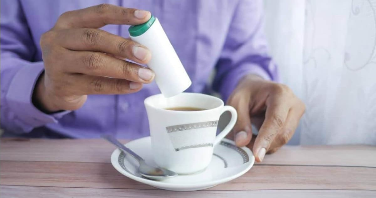 A photo of a man adding sugar in their coffee, in a table
