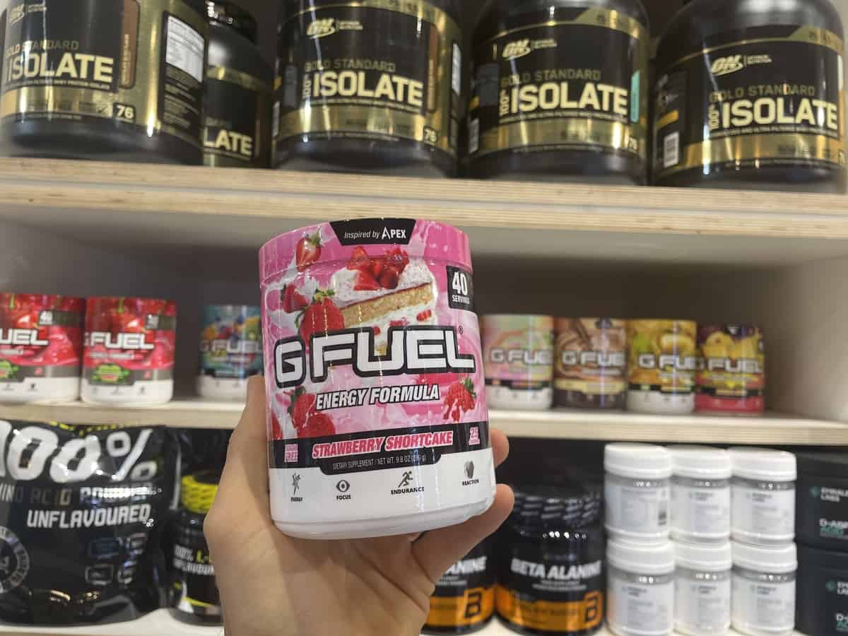 G Fuel Strawberry Shortcake energy tub held in hand with different flavors of G Fuel in background