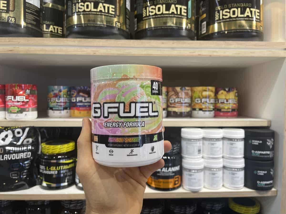 G Fuel Rainbow Sherbet energy tub held in hand with different flavors of G Fuel in background