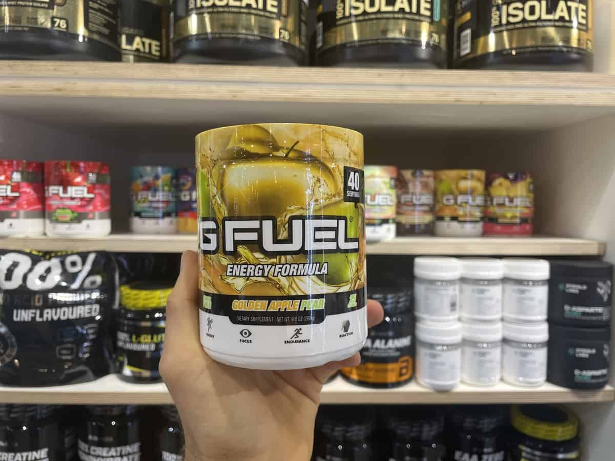 G Fuel Golden Apple Pear energy tub held in hand with different flavors of G Fuel in background