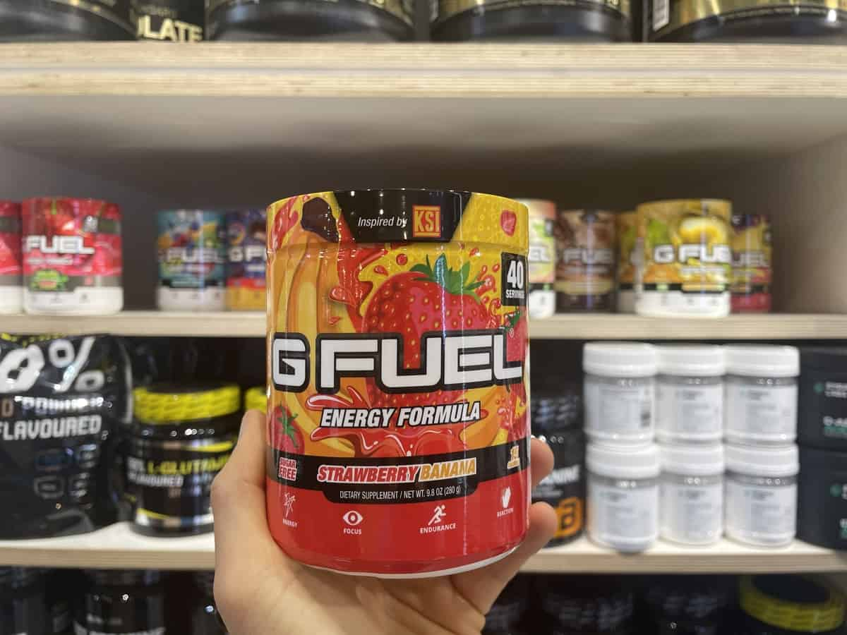 G Fuel Strawberry Banana energy tub held in hand with different flavors of G Fuel and supplements in background