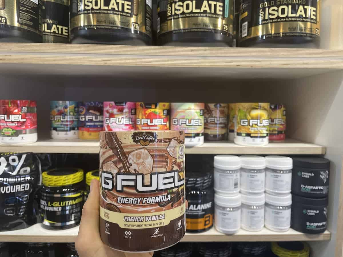 G Fuel French Vanilla energy tub held in hand with different flavors of G Fuel and supplements in background