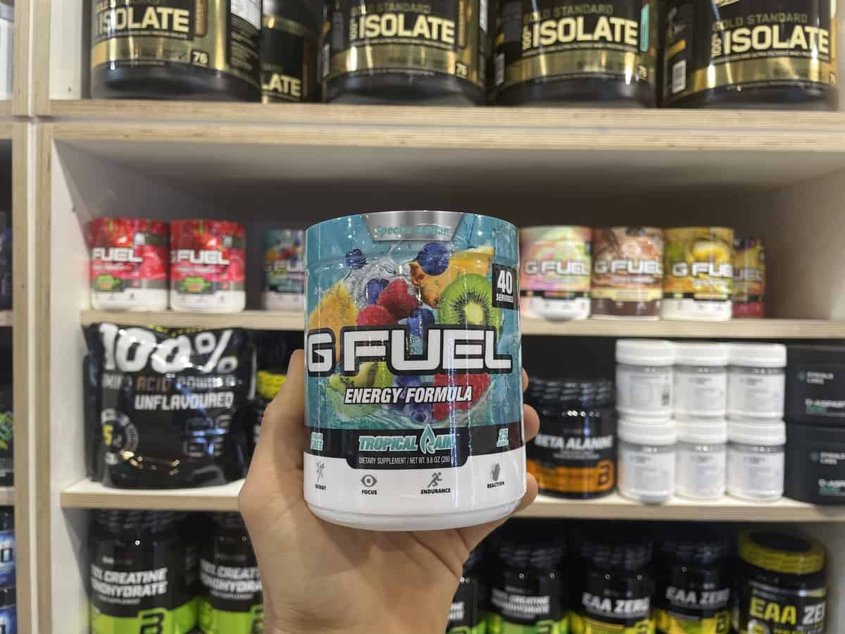 G Fuel Tropical Rain energy tub held in hand with different flavors of G Fuel and supplements in background