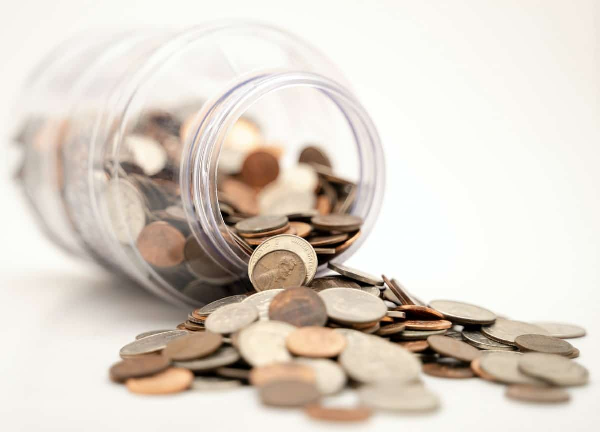 A photo of coins spilling out of a jar